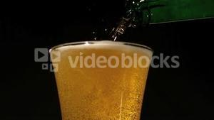 Bottle pouring beer into glass