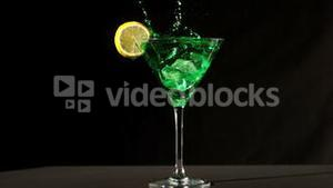 Ice cube falling into green cocktail