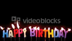 Colourful happy birthday candles being blown out with copy space on black background
