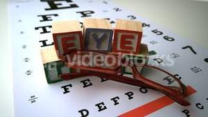 Glasses falling onto eye test with blocks spelling out eye test