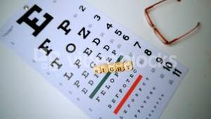 Dice spelling out sight falling onto eye test beside glasses