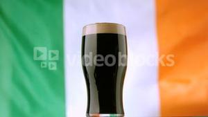 Pint of Irish stout on background of irish flag waving
