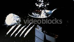 White drugs falling onto spoon beside lines larger pile and lighter