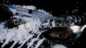 Syringe falling on white drug while drug is cooking on spoon