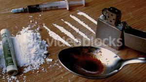 Rolled up note falling on white substance with lines lighter syringe and cooking spoon