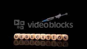 Syringe falling and rolling over dice spelling medication