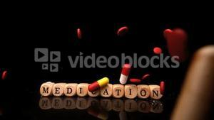 Pills falling and rolling over dice spelling medication
