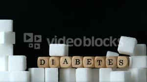 Sugar cubes and dice spelling diabetes falling down in black background over sugar cubes wall
