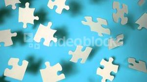 Jigsaw puzzle falling on blue surface