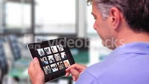 Man using tablet to view business people at work
