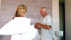 Mature couple having a pillow fight and laughing