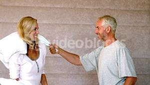 Mature couple pillow fighting at home