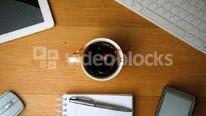 Sugar cubes falling into cup of coffee and splashing a tablet pc