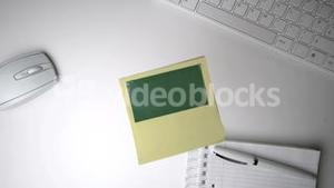 Yellow post it with green copy space falling on office desk
