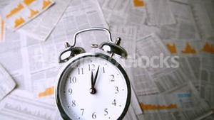Ringing alarm clock falling over sheets of paper