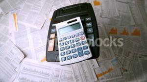 Calculators falling over sheets of paper