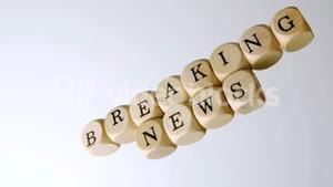 Breaking news spelled out in dice falling on white surface