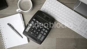 Calculator falling on office desk in black and white