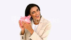 Businesswoman shaking piggy bank