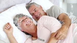 Couple talking and laughing in the bed
