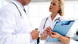 Doctors discussing and writing on a folder