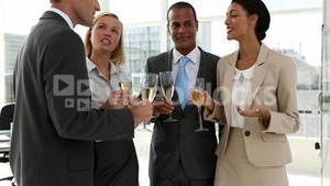Business people celebrating with champagne and chatting