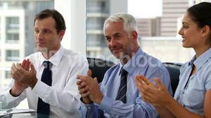 Business people clapping sitting in board room