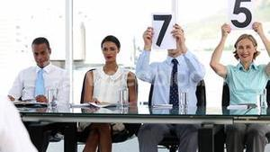 Business people showing grades one by one