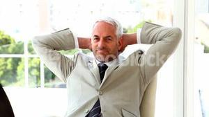 Confident businessman relaxing on his chair