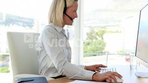 Blonde haired businesswoman working with a headset