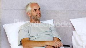 Man sitting in his bed while watching television