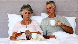 Mature couple enjoying breakfast in bed