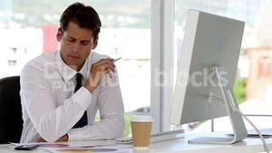 Businessman examining documents helped by his computer