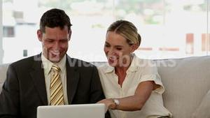 Laughing colleagues looking at a laptop