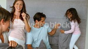Smiling family having a pillow fight