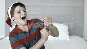 Happy boy using party popper in the bedroom in black and white
