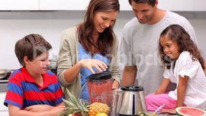 Mother making smoothie for her family