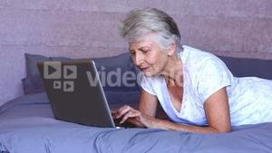 Woman lying on bed using laptop