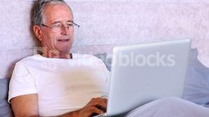 Elderly man using laptop in bed