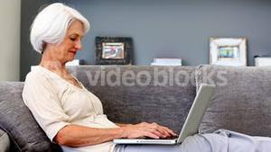 Old woman using laptop on couch