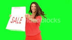 Woman revolving while showing a shopping bag on green screen