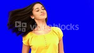 Smiling woman tossing her hair on blue screen