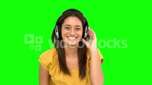 Woman smiling and listening to music on green screen