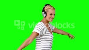 Young woman listening to music on green screen
