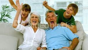 Grandparents and children raising their arms in the living room