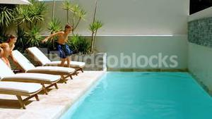 Happy siblings diving into the swimming pool