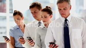 Business people standing in line with their smartphones
