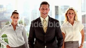 Three smiling business people posing