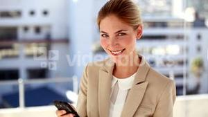 Portrait of smiling businesswoman text messaging