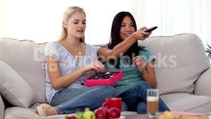 Friends watching TV together while eating chocolates